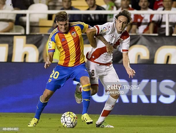 Valencia's Argentinian forward Rodrigo de Paul vies with Rayo's midfielder Jose Raul Baena during the Spanish league football match Rayo Vallecano de...