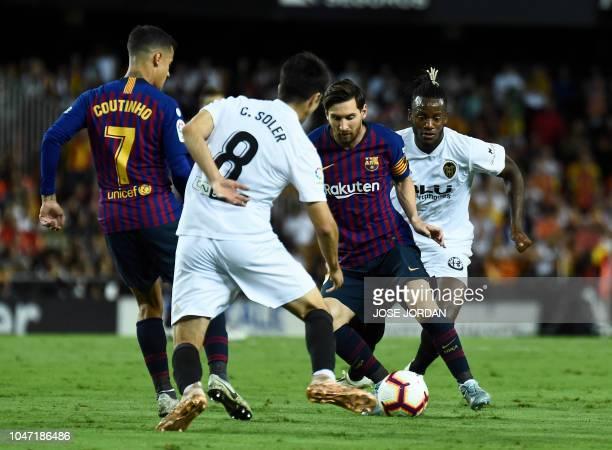 Valencia's Belgian forward Michy Batshuayi and Valencia's Spanish midfielder Carlos Soler vie with Barcelona's Argentinian forward Lionel Messi...