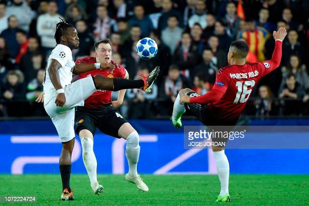 Valencia's Belgian forward Michy Batshuayi challenges Manchester United's English defender Phil Jones and Manchester United's Argentinian defender...