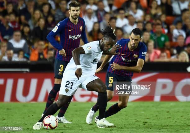 Valencia's Belgian forward Michy Batshuayi vies with Barcelona's Spanish defender Gerard Pique and Barcelona's Spanish midfielder Sergio Busquets...