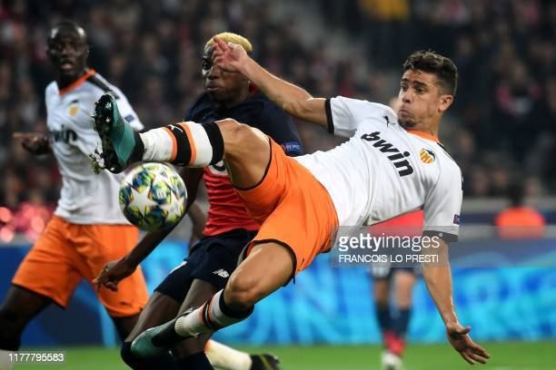 Valencia's Brazilian defender Gabriel Paulista jumps for the ball as he vies with Lille's Nigerian forward Victor Osimhen during the UEFA Champions...