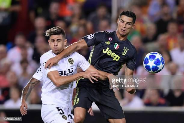 TOPSHOT Valencia's Brazilian defender Gabriel Paulista vies with Juventus' Portuguese forward Cristiano Ronaldo during the UEFA Champions League...
