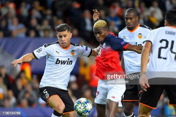 Valencia's Brazilian defender Gabriel Paulista vies with Lille's Nigerian forward Victor Osimhen during the UEFA Champions League group H football...