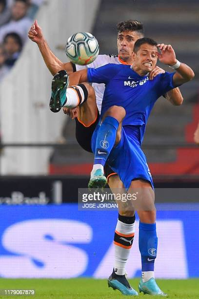 Valencia's Brazilian defender Gabriel Paulista vies with Sevilla's Mexicain forward Chicharito during the Spanish league football match between...