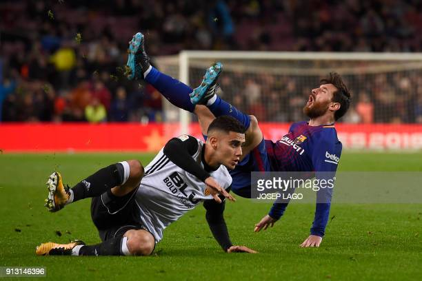 Valencia's Brazilian forward Andreas Pereira clashes with Barcelona's Argentinian forward Lionel Messi during the Spanish 'Copa del Rey' first leg...