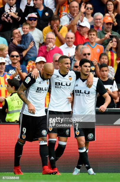 Valencia's Brazilian forward Rodrigo Moreno celebrates a goal with Valencia's Portuguese forward Goncalo Guedes and Valencia's Italian forward Simone...