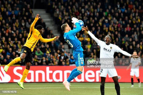 Valencia's Brazilian goalkeeper Neto catches the ball in front of Young Boys' Ivorian forward Roger Assale during the UEFA Champions League Group H...
