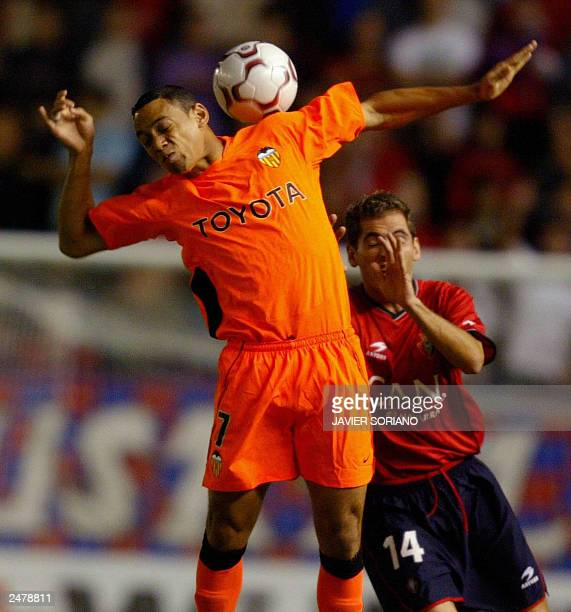 Valencia's Brazilian player Oliveira fights for the ball with Osasuna's Josetxo during their spanish league match at the El Sadar stadium in Pamplona...