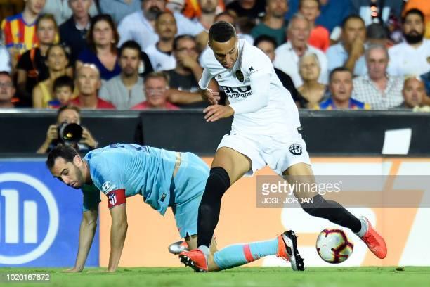 Valencia's Brazilianborn Spanish forward Rodrigo Moreno challenges Atletico Madrid's Uruguayan defender Diego Godin during the Spanish League...