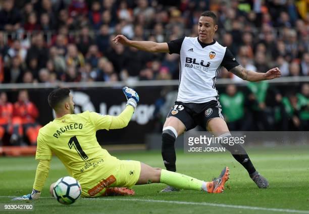 Valencia's Brazilianborn Spanish forward Rodrigo Moreno shoots in front of Alaves' Spanish goalkeeper Fernando Pacheco to score a goal during the...