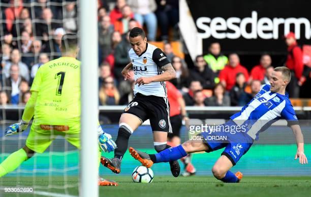 Valencia's Brazilianborn Spanish forward Rodrigo Moreno vies with Alaves' Brazilian defender Rodrigo Ely during the Spanish League football match...