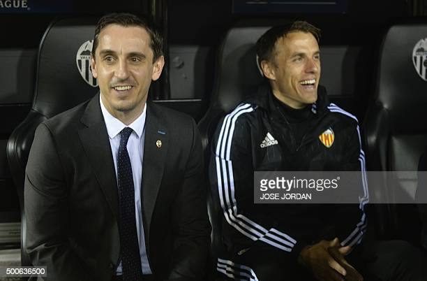 Valencia's British coach Gary Neville and brother and assistant coach Phil Neville smile from the sidelines during the UEFA Champions League football...
