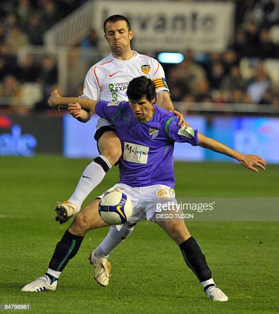 Valencia's Carlos Marchena vies for the ball with Malaga's Alberto Luque during their Spanish league football match at Mestalla Stadium in Valencia...
