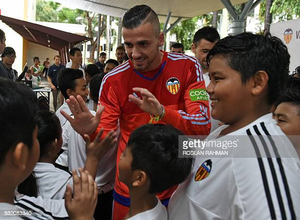 Valencia's CF Spanish footballer Jaume Domenech is greeted by children during a neighbourhood youth community event at Bukit Ho Swee in Singapore on...