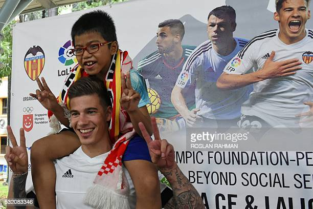 Valencia's CF Spanish footballer Santi Mina carries a boy on his shoulders during a neighbourhood youth community event at Bukit Ho Swee in Singapore...