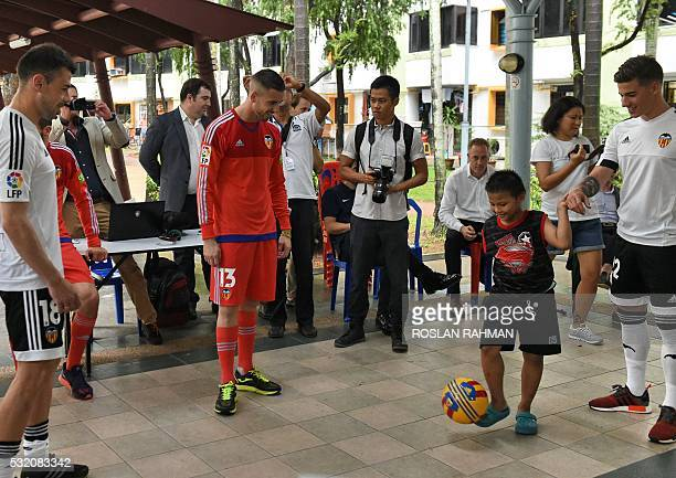 Valencia's CF Spanish footballers Javi Fuego Jaume Domenech and Santi Mina look on while a boy kicks the ball during a neighbourhood youth community...