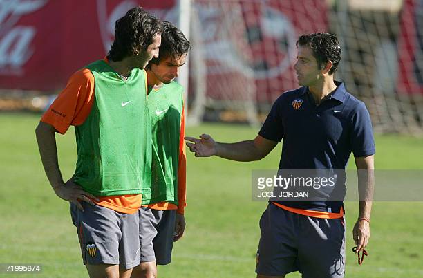 Valencia's coach Quique Flores speaks with Argentinian Fabian Ayala and Italian Emiliano Moretti during a training session on the eve of their...