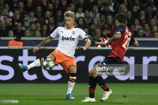 Valencia's Danish midfielder Daniel Wass and Lille's Croatian defender Domagoj Bradaric vie for the ball during the UEFA Champions League Group H...