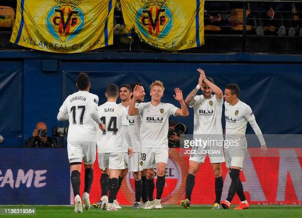 Valencia's Danish midfielder Daniel Wass celebrates his goal with teammates during the UEFA Europa league quarter final first leg football match...
