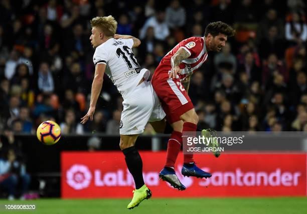 Valencia's Danish midfielder Daniel Wass challenges Girona's Spanish defender Carles Planas during the Spanish league football match between Valencia...