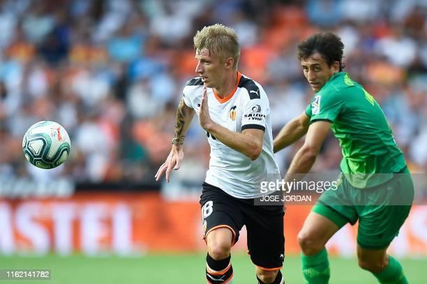 Valencia's Danish midfielder Daniel Wass challenges Real Sociedad's Spanish midfielder Mikel Oiarzabal during the Spanish League football match...