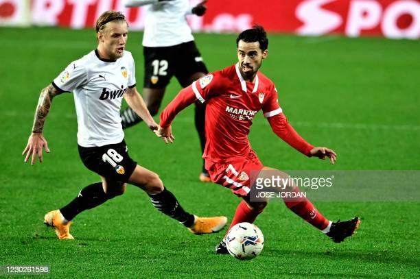 Valencia's Danish midfielder Daniel Wass challenges Sevilla's Spanish midfielder Alez Vidal during the Spanish league football match between Valencia...