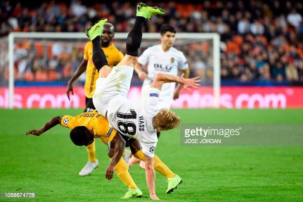 Valencia's Danish midfielder Daniel Wass falls over Young Boys' Ivorian forward Roger Assale during the UEFA Champions League group H football match...