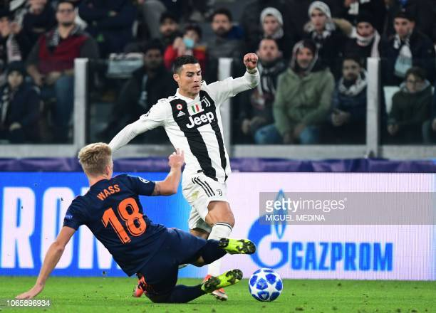 Valencia's Danish midfielder Daniel Wass tackles Juventus' Portuguese forward Cristiano Ronaldo during the UEFA Champions League group H football...