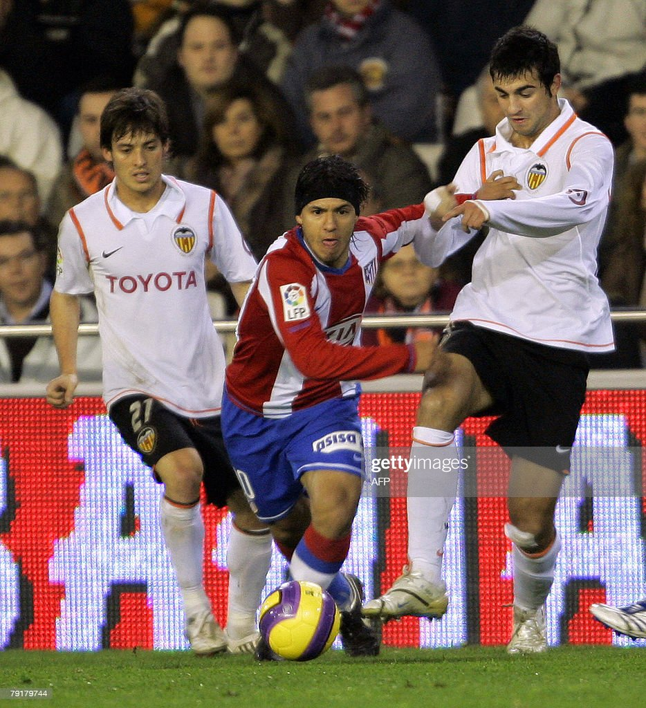 Valencia's David Silva (L) and Raul Albiol figths for the ball with Atletico Madrid's Argentinian Kun Aguero during their Spanish King cup football match at Mestalla Stadium in Valencia, 23 January 2008.