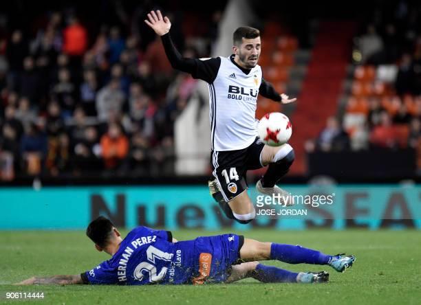 Valencia's defender Jose Gaya jumps over Alaves Paraguayan forward Hernan Perez during the Spanish 'Copa del Rey' football match between Valencia CF...