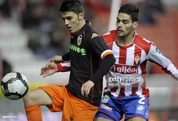 Valencia's forward David Villa vies with Sporting Gijon's defender Alberto Botia during their Spanish first league football match at the Molinon...
