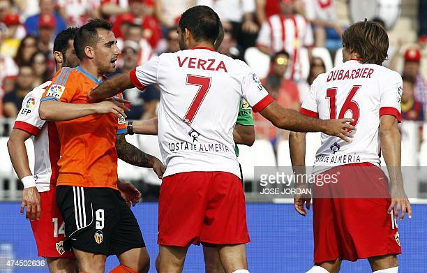 Valencia's forward Paco Alcacer argues with Almeria's midfielder Verza and Almeria's Argentinian defender Sebastian Dubarbier during the Spanish...
