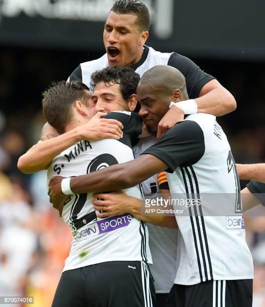 Valencia's forward Santi Mina celebrates a goal with Valencia's Spanish midfielder Dani Parejo Valencia's Colombian defender Jeison Murillo and...