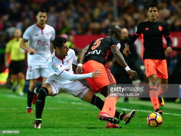 Valencia's French defender Eleaquim Mangala vies with Sevilla's defender Sergio Escudero during the Spanish league football match Sevilla FC vs...