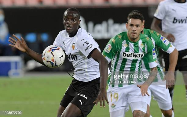 Valencia's French defender Mouctar Diakhaby challenges Real Betis' Paraguayan forward Arnaldo Sanbria during the Spanish League football match...