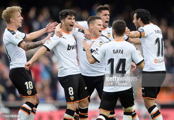 Valencia's French forward Kevin Gameiro celebrates with teammates after scoring a goal during the Spanish League football match between Valencia and...