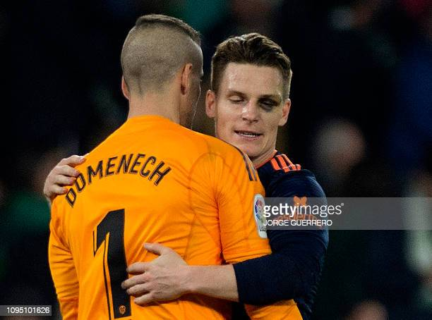 Valencia's French forward Kevin Gameiro hugs teammate Spanish goalkeeper Jaume Domenech at the end of the Spanish Copa del Rey semifinal first leg...