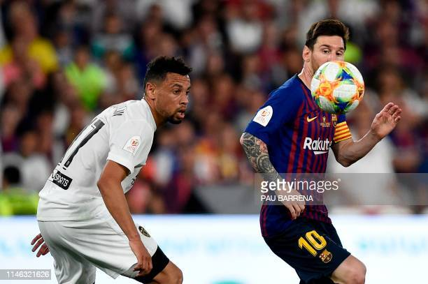 Valencia's French midfielder Francis Coquelin and Barcelona's Argentinian forward Lionel Messi eye the ball during the 2019 Spanish Copa del Rey...