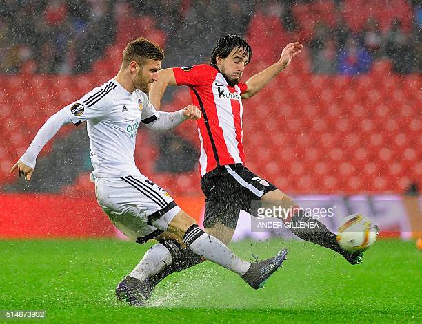 Valencia's German defender Shkodran Mustafi vies with Athletic Bilbao's midfielder Benat Etxebarria during the UEFA Europa League Round of 16 first...