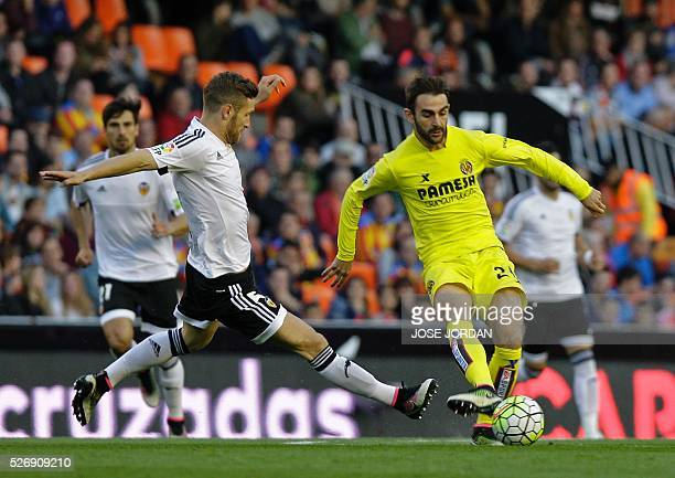 Valencia's German defender Shkodran Mustafi vies with Villarreal's forward Adrian Lopez during the Spanish league football match Valencia CF vs...