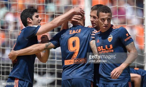 Valencia's Italian forward Simone Zaza celebrates a goal with Valencia's Portuguese forward Goncalo Guedes and Valencia's Brazilianborn Spanish...