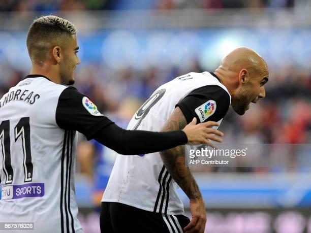 Valencia's Italian forward Simone Zaza celebrates with his teammate Brazilian forward Andreas Pereira during the Spanish league football match...