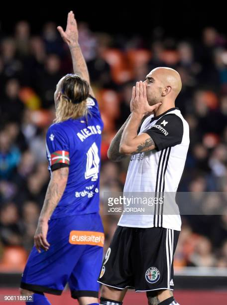 Valencia's Italian forward Simone Zaza gestures beside Alaves' Spanish defender Alexis Ruano after missing an attempt on goal during the Spanish...