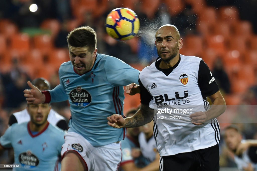Valencia's Italian forward Simone Zaza (R) heads the ball during the Spanish league football match between Valencia and Celta Vigo at the Mestalla Stadium in Valencia on December 9, 2017. /