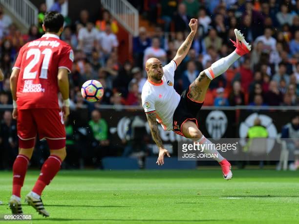 Valencia's Italian forward Simone Zaza jumps to kick the ball during the Spanish league football match Valencia CF vs Sevilla FC at the Mestalla...