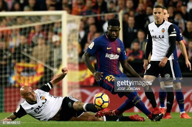 Valencia's Italian forward Simone Zaza vies with Barcelona's French defender Samuel during the Spanish league football match Valencia CF and FC...