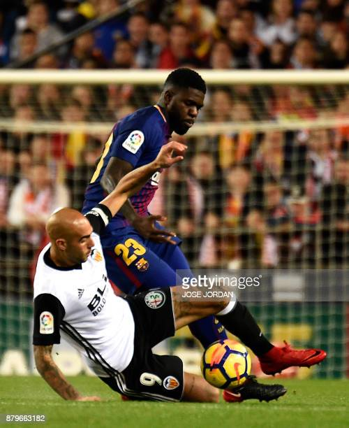 Valencia's Italian forward Simone Zaza vies with Barcelona's French defender Samuel Umtiti during the Spanish league football match Valencia CF and...
