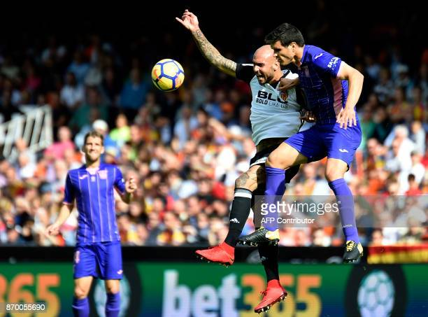 Valencia's Italian forward Simone Zaza vies with Leganes' Argentinian midfielder Alexander Szymanowski during the Spanish league footbal match...