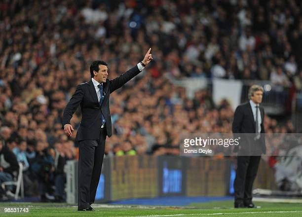 Valencia's manager Unay Emery instructs his team from the sideline beside Real Madrid manager Manuel Pellegrini during the La Liga match between Real...