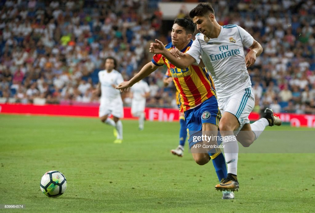 Valencia's midfielder Alvaro Medran (L) vies with Real Madrid's midfielder Marco Asensio during the Spanish league football match Real Madrid CF vs Valencia CF at the Santiago Bernabeu stadium in Madrid on August 27, 2017. The game ended with a draw 2-2. /